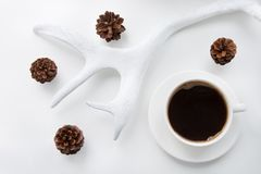 Christmas and winter concept. White mug of hot black coffee and cones, horns on white background. Top view. Stock Photos