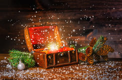 Christmas winter fairy with fantasy miracle in opened chest treasure. Background of mystery gift New Year, fir tree and snow. royalty free stock image