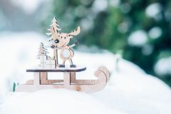 Christmas winter holiday festive background. Wooden cute reindeer on sled, red gift boxes on white snow and green christmas trees outdoor. Christmas royalty free stock images