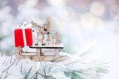 Christmas winter holiday greeting card. Wooden cute reindeer on sled, red gift boxes on white snow and green christmas trees outdoor. Christmas composition stock photography
