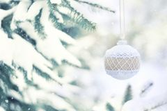 Christmas winter holiday greeting card. White rustic Christmas ornament ball with burlap on green christmas trees with snow royalty free stock photography