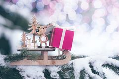 Christmas winter holiday greeting card. Wooden cute reindeer on sled, red gift boxes on white snow and green christmas trees outd. Oor. Christmas composition royalty free stock photo
