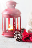 Christmas or winter home concept with lantern, fir cones, snow and warm wear. Stock Photos