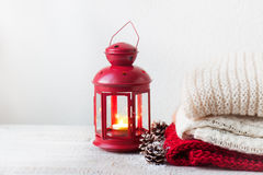 Christmas or winter home concept with lantern, fir cones, snow and warm wear. Stock Photography