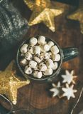 Christmas winter hot chocolate with marshmellows served with light garland. Christmas or New Year winter hot chocolate with marshmallows and gingerbread cookies Stock Images