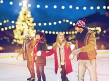 Happy friends at christmas skating rink Stock Images