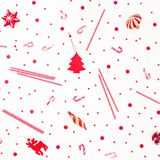 Christmas winter pattern of candy cane and shiny confetti on white background. Flat lay, top view. New year concept royalty free stock images