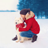 Christmas, winter and people concept - happy woman owner embracing white Samoyed dog outdoors royalty free stock image