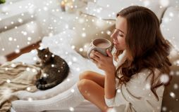 Happy woman with cup of coffee in bed at home Royalty Free Stock Images