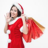 Christmas winter shopping. Asian woman in santa claus hat standing holding shopping bags Royalty Free Stock Images