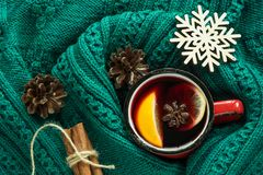 Christmas and winter traditional hot beverage. Mulled wine in red mug with spice wrapped in warm green sweater. Stock Photos