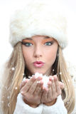 Christmas winter woman. Young woman blowing winter snow at christmas or winter vacation Stock Image