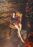 Christmas winter woman with christmas presents. Fairy Beautiful Christmas and Christmas tree Festive make-up. Fashion model girl w Royalty Free Stock Images
