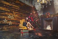 Christmas winter woman with christmas presents. Fairy Beautiful Christmas and Christmas tree Festive make-up. Fashion model girl w Royalty Free Stock Photos