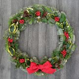 Christmas and Winter Wreath. With holly, mistletoe, ivy, spruce fir, pine cones and a red bow on rustic grey wood background stock image