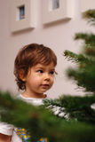 Christmas wish. A little girl making a wish in front of a Christmas tree Royalty Free Stock Photo