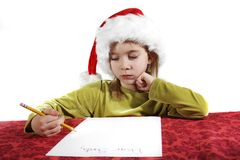 Christmas wish list. A young girl child writing her wish list to santa. Dear Santa on her otherwise blank piece of paper. Red table cloth, with an isolate white Stock Photo