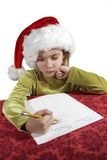 Christmas wish list. A young girl child writing her wish list to santa. Dear Santa on her otherwise blank piece of paper. Red table cloth, with an isolate white Stock Photography