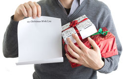 Christmas wish list. Man holding his Christmas wis hlist and presents Stock Photo