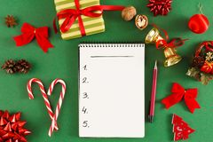 Christmas wish list. Empty notepad at messy table background. Christmas wish list or letter to Santa. Notepad with copy space on green messy table background Stock Photos