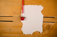 Christmas wish list. Parchment for a Christmas wish list against a rustic wooden background Royalty Free Stock Photo