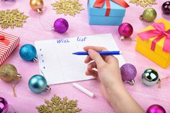 Christmas wish list on pink background. Gift boxes, golden snowflakes, colorful baubles. Flat lay. Woman hand writing letter Royalty Free Stock Photography