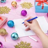 Christmas wish list on pink background. Gift boxes, golden snowflakes, colorful baubles. Flat lay. Woman hand writing letter Royalty Free Stock Image