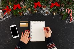 Christmas wish list on white wood table background. Christmas wish list writing. Woman creating present list for winter holidays. Top view, preparing for xmas Royalty Free Stock Image