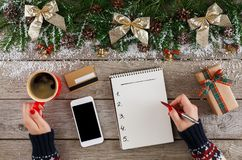Christmas wish list on white wood table background. Christmas wish list writing. Woman creating present list for winter holidays. Top view, preparing for xmas Stock Image