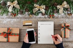 Christmas wish list on white wood table background. Christmas wish list writing. Woman creating present list for winter holidays. Top view, preparing for xmas Stock Photography