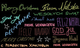 Christmas wishes. Merry Christmas - holiday wishes doodle in multiple languages. Christmas background Royalty Free Stock Photo