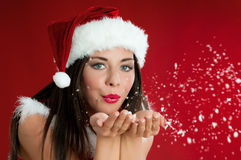 Christmas wishes. Beautiful santa claus girl blowing white snowflakes from her hands on red christmas background
