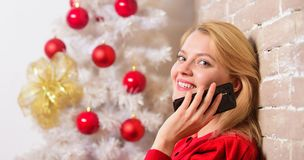 Christmas wishes concept. Woman pretty peaceful dreamy face hold smartphone enjoy mobile phone conversation. Girl near. Christmas tree close up. Waiting for stock images