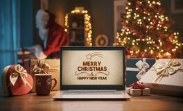 Free Christmas Wishes On A Laptop And Santa Bringing Gifts At Home Stock Photos - 201864883