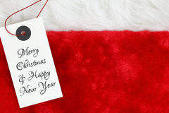 Christmas wishes. On white tag on santas red fur stock photos