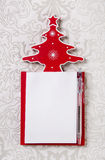 Christmas wishlist: white and red writing pad with a tree. Stock Photos