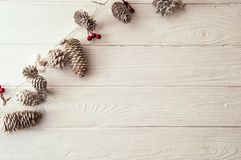 Christmas woden background. Christmas decorative garland, diagonal to the boards, with red and white berries, snowy fir cones. Top view, flat lay. Christmas royalty free stock image