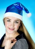 Christmas woman. Beautiful christmas woman in santa hat on blue background Stock Photo