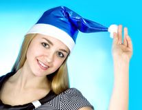 Christmas woman. Beautiful christmas woman in santa hat on blue background Stock Image
