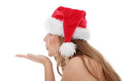 Christmas woman. Wearing a santa hat sendind a kiss, isolated on white background Royalty Free Stock Image