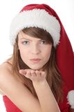 Christmas woman. Wearing a santa hat sendind a kiss, isolated on white background Stock Image