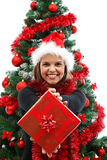 Christmas woman. Young attractive woman with a gift near the Christmas tree Royalty Free Stock Image