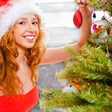 Christmas woman. Near a Christmas tree holding Christmas toy while decorating Christmas tree stock photography