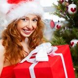 Christmas woman. Near a Christmas tree holding big gift box while sitting near Christmas Tree royalty free stock image