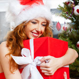 Christmas woman. Near a Christmas tree holding big gift box while sitting near Christmas Tree royalty free stock photography