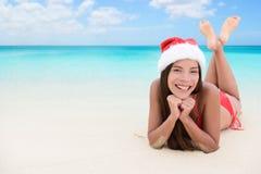 Christmas woman on beach winter vacation. Christmas woman relaxing during winter beach holidays. Girl smiling at camera during travel vacation wearing a santa Stock Photography