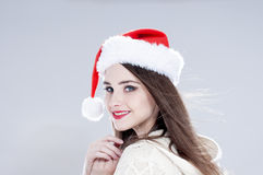 Christmas woman. Beautiful charming girl wearing  santa hat over Stock Images