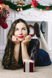 Christmas Woman. Beauty Model Girl with Fireplace on Background.  Gift in Hand. Open Mouth Beautiful Teeth Smile. True Royalty Free Stock Photos
