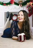 Christmas Woman. Beauty Model Girl with Fireplace on Background.  Gift in Hand. Open Mouth Beautiful Teeth Smile. True. Christmas Woman. Beauty Model Girl with Royalty Free Stock Photo