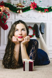 Christmas Woman. Beauty Model Girl with Fireplace on Background.  Gift in Hand. Open Mouth Beautiful Teeth Smile. True. Christmas Woman. Beauty Model Girl with Royalty Free Stock Photography